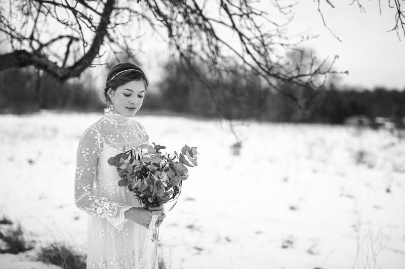 Winterbraut im Schnee mit Brautstrauß
